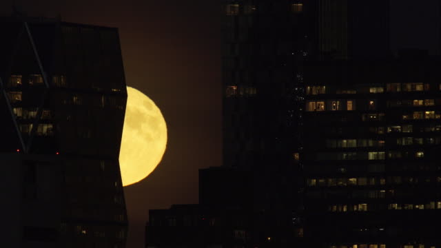Time lapse of bright full moon rising behind New York City skyscraper lit from the inside