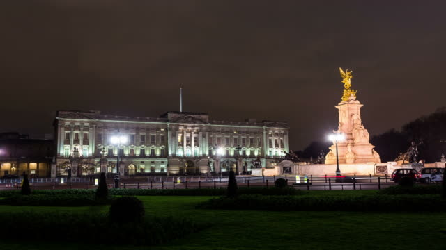 london circa 2013: time lapse of buckingham palace by night, with traffic and clouds in london. - buckingham stock videos & royalty-free footage