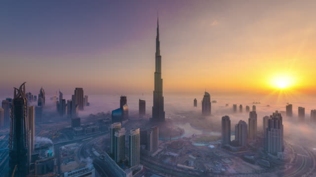 vídeos de stock e filmes b-roll de time lapse of burj khalifa covered in a sea of fog at dawn - arranha céu