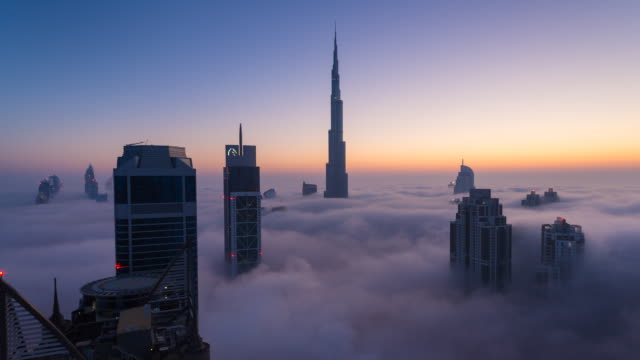 vídeos de stock e filmes b-roll de time lapse of burj khalifa rising above fog at dawn, night to day - arranha céu