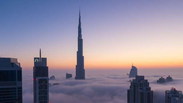 Time Lapse of Burj Khalifa rising above fog at dawn, night to day, zoom out