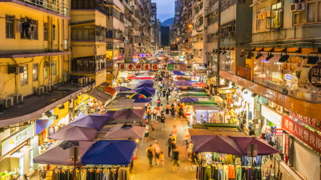 vidéos et rushes de time lapse of busy market street in mong kok by night, hong kong - mong kok