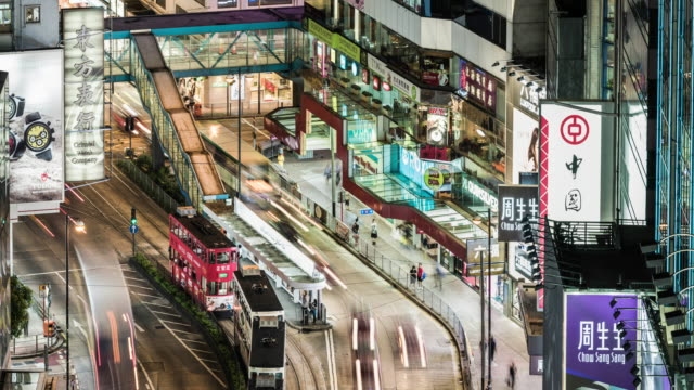 time lapse of busy road in hong kong island with trams passing through - hong kong island stock videos & royalty-free footage