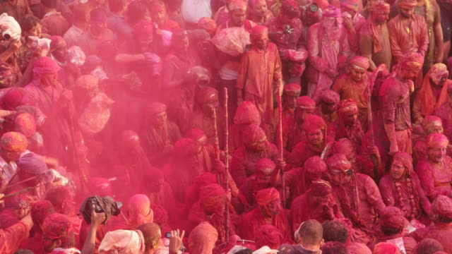 Time lapse of camera person photogrpahing people chanting prayers in a temple during Holi, festival of colors