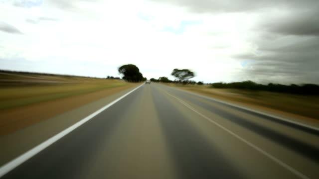 time lapse of car driving (away from sunset) - förarperspektiv bildbanksvideor och videomaterial från bakom kulisserna