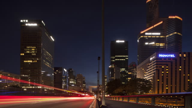 stockvideo's en b-roll-footage met time lapse of car traffic at night on bridge driving to la défense business / financial district of paris - lichtspoor lange sluitertijd