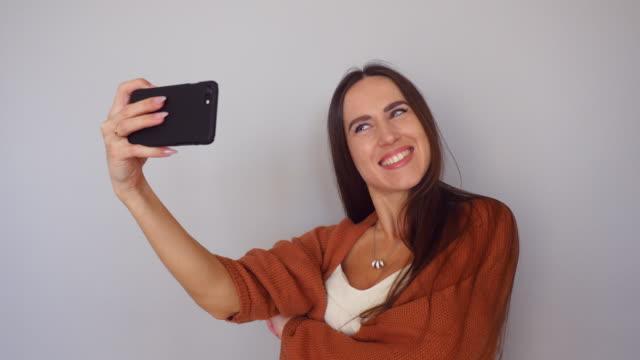 Time lapse of cheerful young female making various combinations for selfie