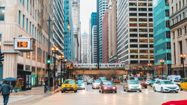 4k time lapse of chicago street with traffic road intersection in rush hour among modern buildings of downtown chicago at michigan avenue in chicago, illinois, united states - chicago 'l' stock videos & royalty-free footage