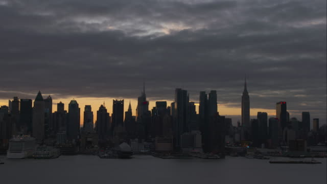 Time lapse of cloud sunrise above New York City skyline view from across Hudson River