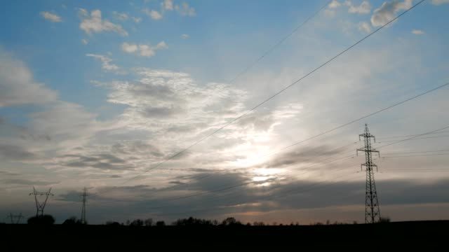 4k time lapse of clouds and electricity, high voltage line, clear blue sky, sun rays, cloudscape, springtime, beauty in nature, freedom, wind, industry, electricity - power equipment stock videos & royalty-free footage