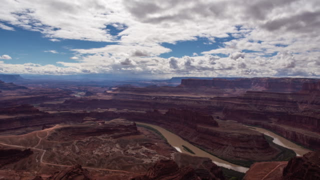 time lapse of clouds and sun illuminating a spectacular canyon landscape in dead horse point state park, utah. - fiume colorado video stock e b–roll
