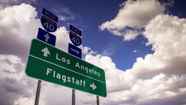 time lapse of clouds behind i-40 sign los angeles-flagstaff - directional sign stock videos & royalty-free footage