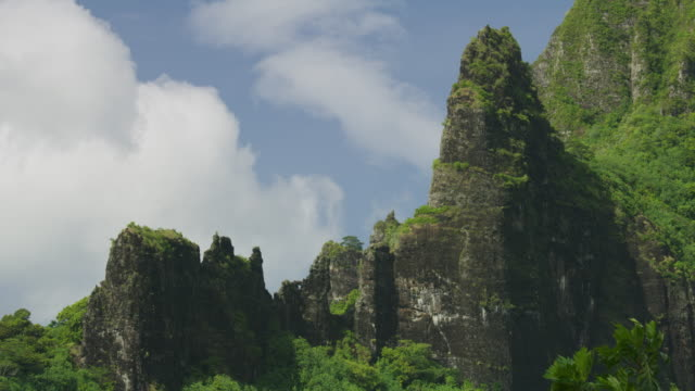 time lapse of clouds blowing over trees on rock formation / moorea, french polynesia - moorea stock videos and b-roll footage