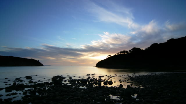 Time lapse of clouds drifting over Schooner Bay at sunset / Great Barrier Island, New Zealand