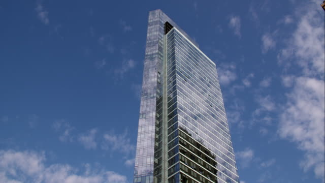 time lapse of clouds moving above and reflecting off of glass a singular skyscraper in new york city - curtain wall facade stock videos and b-roll footage