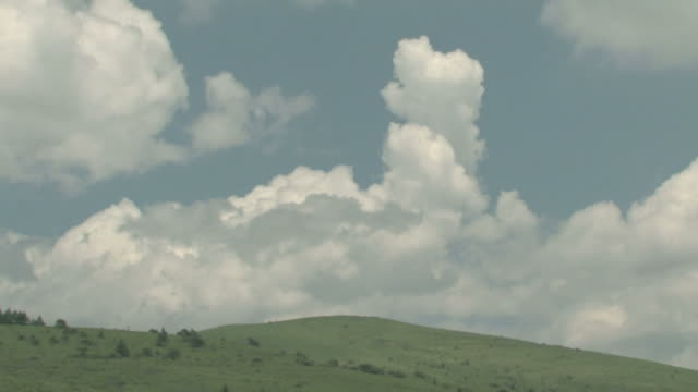 Time lapse of clouds moving over hill