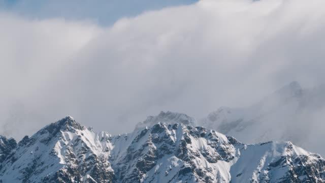 vidéos et rushes de laps de temps de nuages se déplaçant au-dessus des montagnes neigeuses, paysage alpin - format hd
