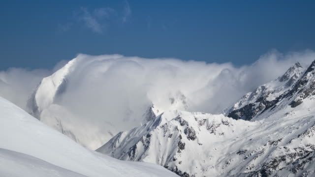 time lapse of clouds moving over snowy mountains, alpine landscape - snowcapped mountain stock videos and b-roll footage