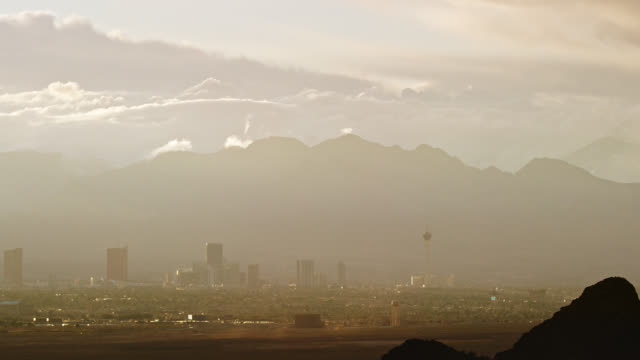 time lapse of clouds rolling over the las vegas city skyline with mountains in the background on a hazy day while dust devils blow over the desert in the foreground at sunset - nevada stock videos & royalty-free footage