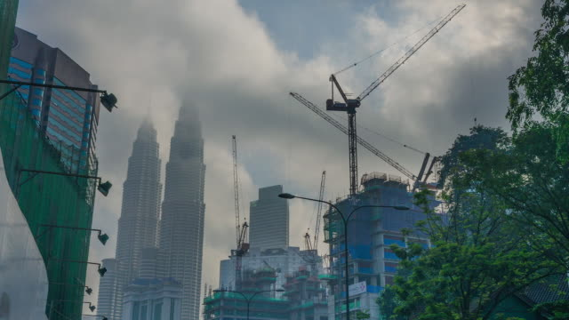 time lapse of clouds scraping the top of the petronas twin towers with construction work underway in the foreground - petronas twin towers stock videos and b-roll footage