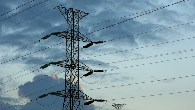 Time lapse of cloudscapes moving behind high voltage pylon