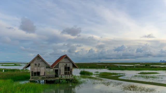 4K Time lapse of cloudy sunset over abandoned house over lake Thale Noi at Phatthalung, Thailand.