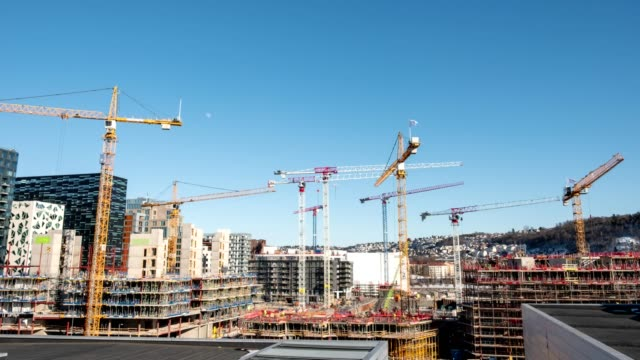 time lapse of construction building with cranes and derrick and blue sky in the city - realizzazione video stock e b–roll