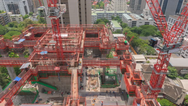 time lapse of construction building with cranes and derrick construction site working in day time - long exposure stock videos & royalty-free footage