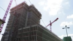 Time Lapse of Construction Cranes Working on Large Building