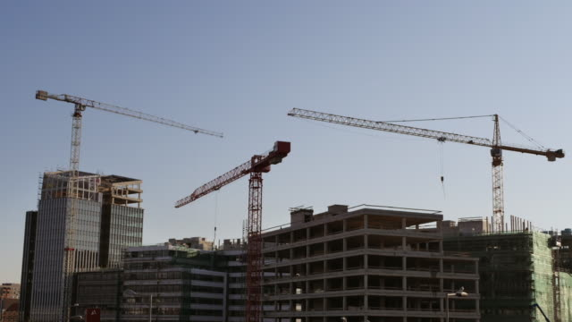 time lapse of construction site with cranes and modern buildings - crane stock videos & royalty-free footage