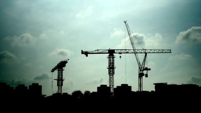 Time lapse of construction tower crane with moving clouds