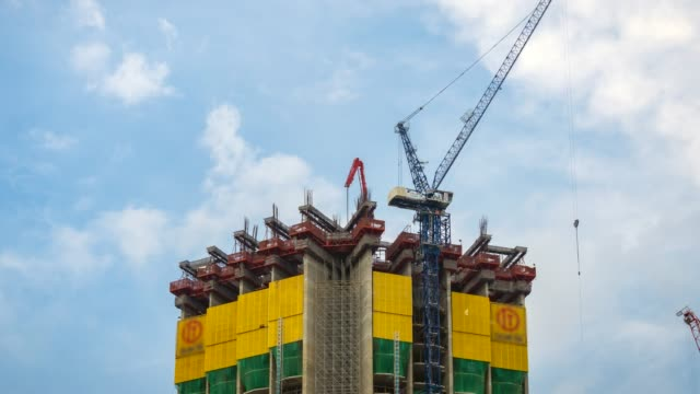 time lapse of crane working in big construction site - hoisting stock videos & royalty-free footage