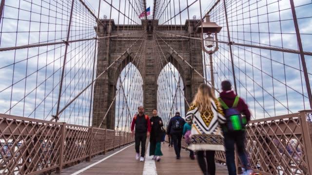 の 4 k の時間の経過、ブルックリン橋、マンハッタン、ニューヨーク市、アメリカ、旅行、ランドマークとビジネスコンセプトでの群衆の匿名の観光ウォーキング - マンハッタン橋点の映像素材/bロール