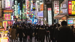 4K Time lapse of crowd pedestrian walking on the shopping neon street cross-walk with car traffic at nighttime in Shinjuku Tokyo city, Japan. Japanese culture and city life concept