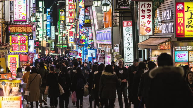 4k time lapse of crowd pedestrian walking on the shopping neon street cross-walk with car traffic at nighttime in shinjuku tokyo city, japan. japanese culture and city life concept - fast motion stock videos & royalty-free footage