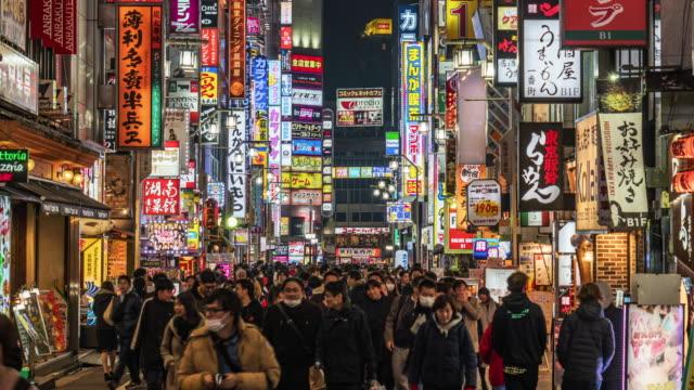 vídeos de stock e filmes b-roll de time lapse of crowd pedestrian walking on the shopping street in shinjuku, tokyo - bairro de shinjuku