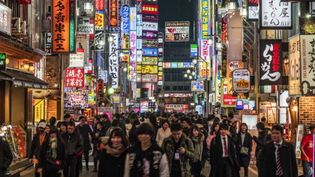 time lapse of crowd pedestrian walking on the shopping street in shinjuku, tokyo - motorway junction stock videos & royalty-free footage