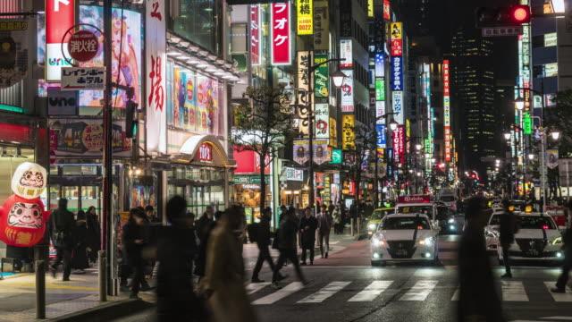 4K Zeitraffer von Crowd Undefined Menschen, die rund um die Nacht Marktstraße rund um den Shimbashi Bahnhof mit Autoverkehr Tokio Stadt, Japan. Japanisches Kultur-und Einkaufsbereichskonzept