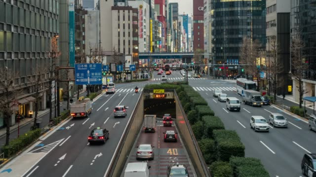 stockvideo's en b-roll-footage met 4k time lapse van menigte ongedefinieerde mensen lopen op de straat cross-walk met autoverkeer en tunnel, in shimbashi station tokyo city in night time, japan. japanse cultuur en winkelen neon street concept - burger menselijke rol