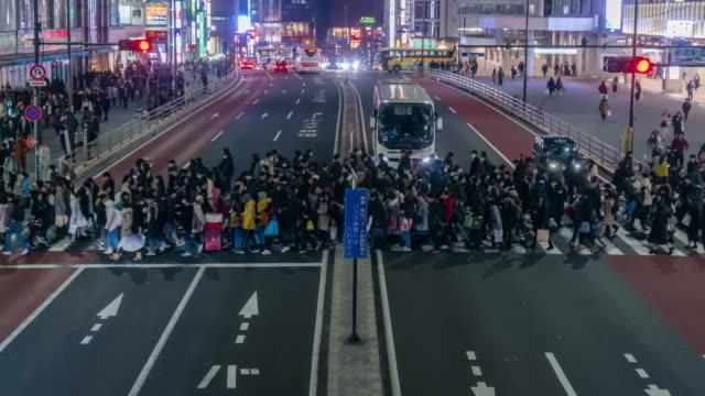 4k zeitraffer von menschen undefiniert menschen zu fuß auf der straße cross-walk mit autoverkehr in shinjuku tokio stadt in der nacht, japan. japanische kultur und shopping neon street konzept - zeitraffer fast motion stock-videos und b-roll-filmmaterial