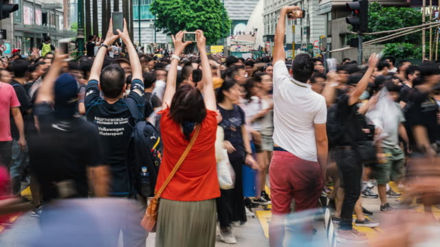 vidéos et rushes de 4k time lapse of crowd unrecognizable protester walking around tsim sha tsui street area, hong kong - démocratie