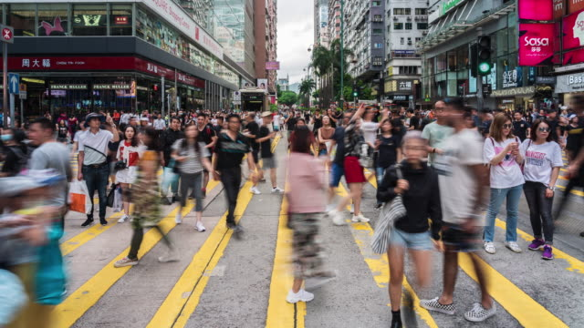 time lapse of crowd unrecognizable protester walking around tsim sha tsui street area, hong kong - marciare video stock e b–roll