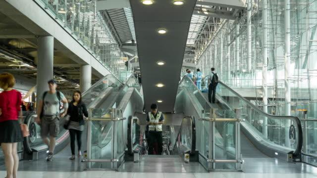 Tid förflutit av publiken gå på rulltrappan på flygplats terminal