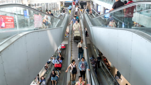 4k time lapse of crowded passenger on walk way escalator airport terminal with baggage - passenger stock videos & royalty-free footage