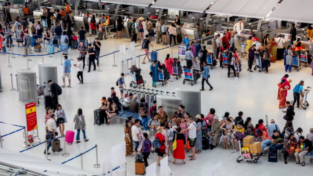 4k time lapse of crowded passenger waiting in line at airport check-in counter in airport terminal with baggage - airport stock videos & royalty-free footage