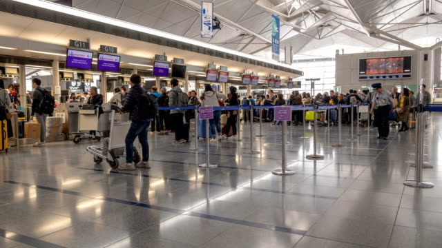 4k time lapse of crowded passenger waiting in line at airport check-in counter in airport terminal with baggage - airport check in counter stock videos & royalty-free footage