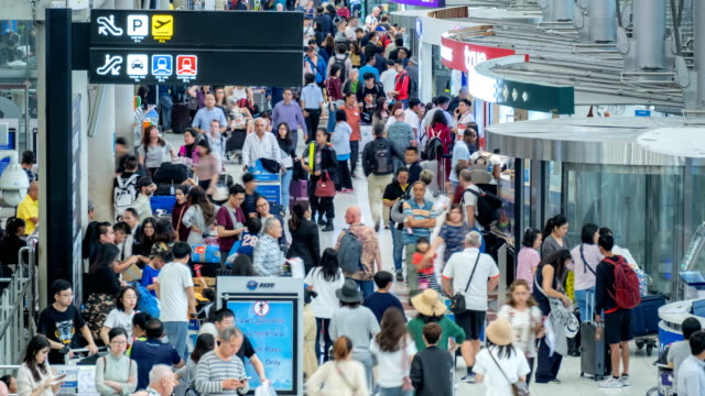 4k time lapse of crowded passenger walking at airport terminal with baggage - luggage stock videos & royalty-free footage