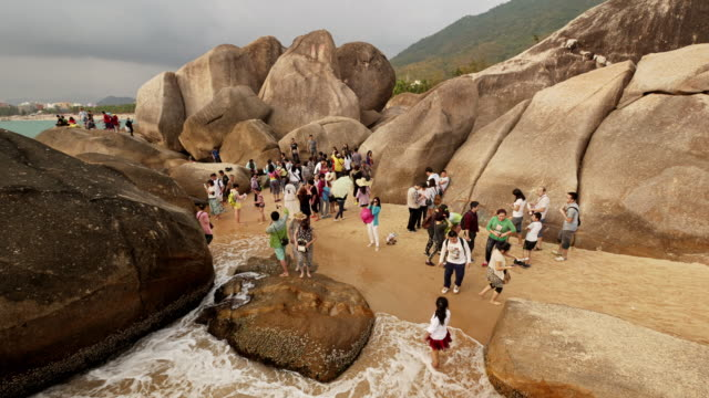 time lapse of crowded tourist attraction end of the earth (tian ya hai jiao) 天涯海角 in sanya,  hainan province, china. wide shot - spoonfilm stock-videos und b-roll-filmmaterial