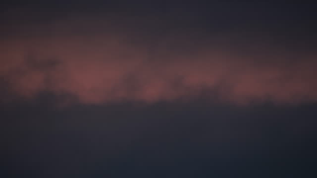 time lapse of dark clouds moving at dusk with orange light behind - storm cloud stock videos & royalty-free footage