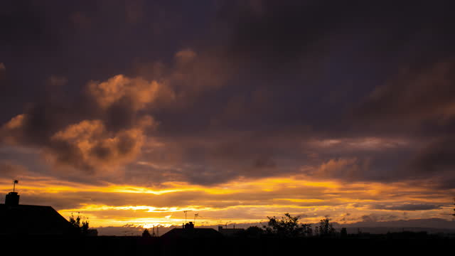 time lapse of dark ominous storm clouds moving over rooftops painted red by the setting sun on october 16, 2020 in bristol, uk. - dramatic sky stock videos & royalty-free footage